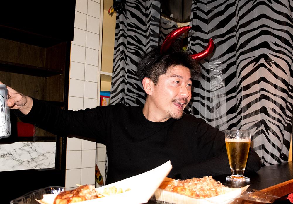 au comptoir du karaoké avec des cornes sur la tête et des takoyaki