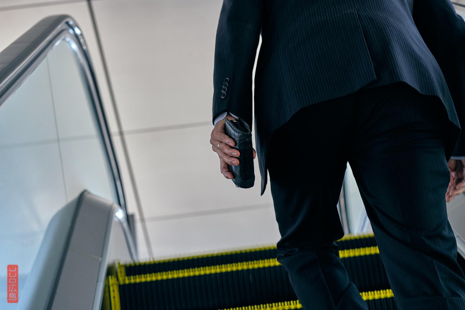 Salaryman dans un escalator, gare d'Hiroshima, Japon