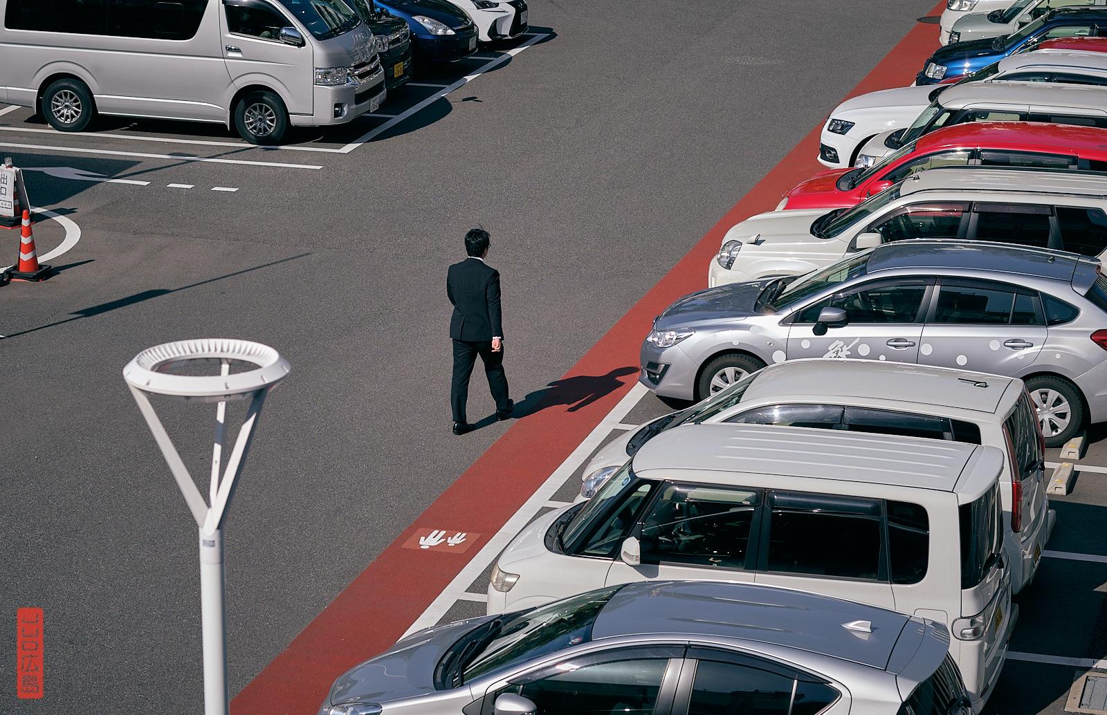 Homme marchant seul sur le parking de la gare d'Hiroshima