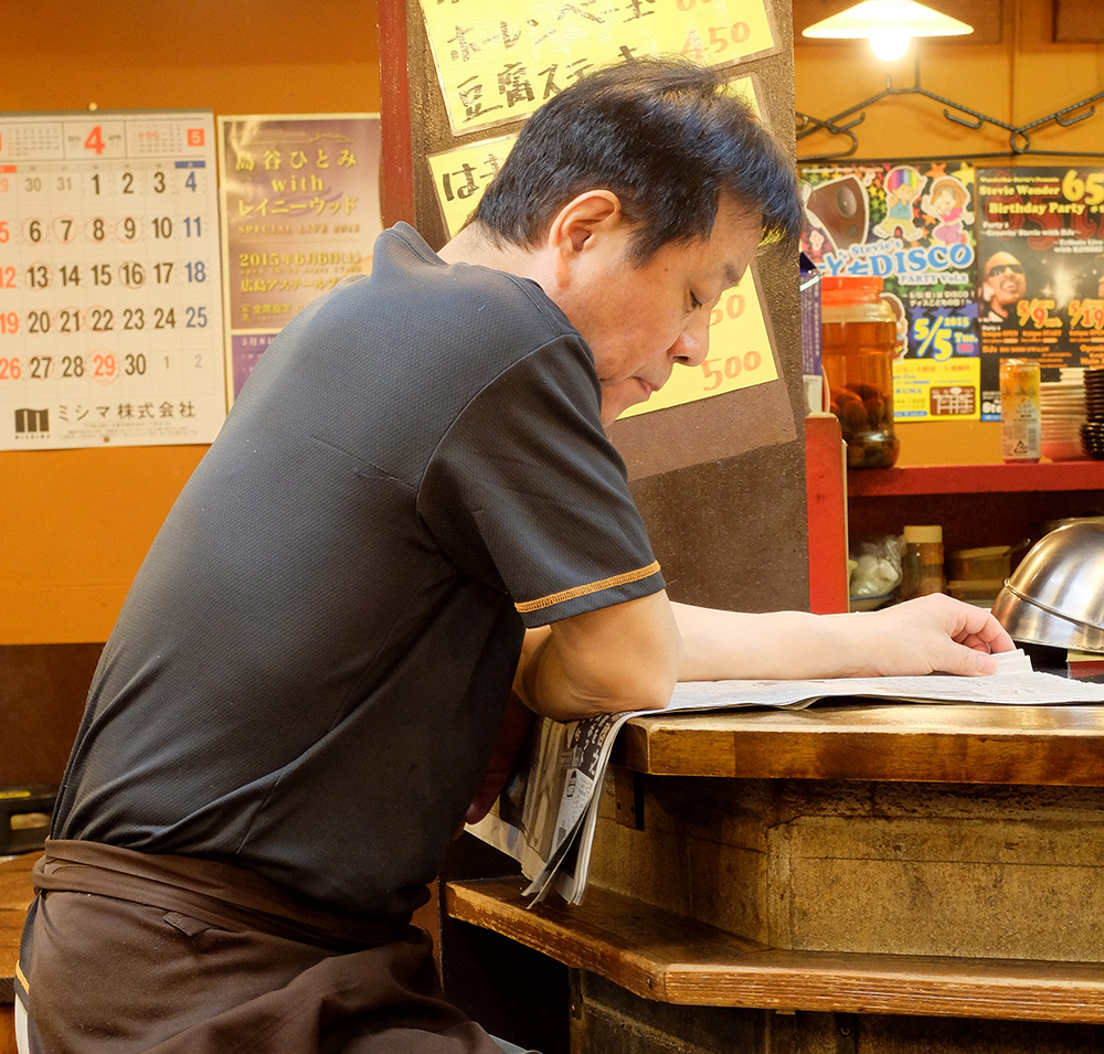 Propriétaire de yatai lisant son journal à Ganko Yatai