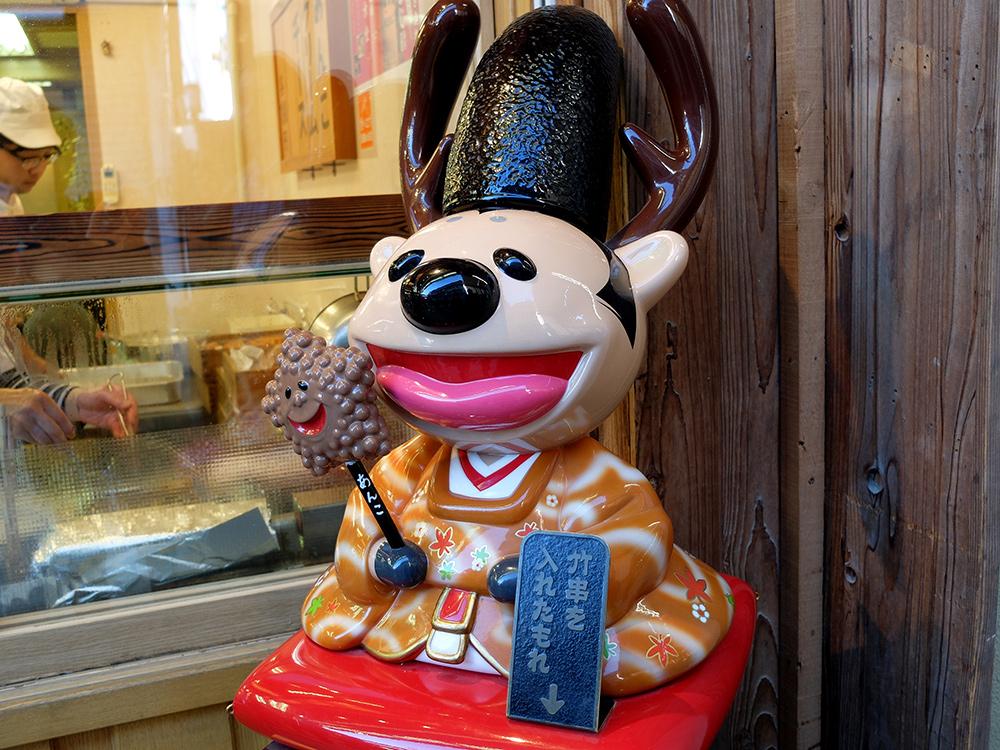 Figurine de biche-prêtre shinto avec un age-momiji-manju (pâtisserie en forme de feuille d'érable frite)