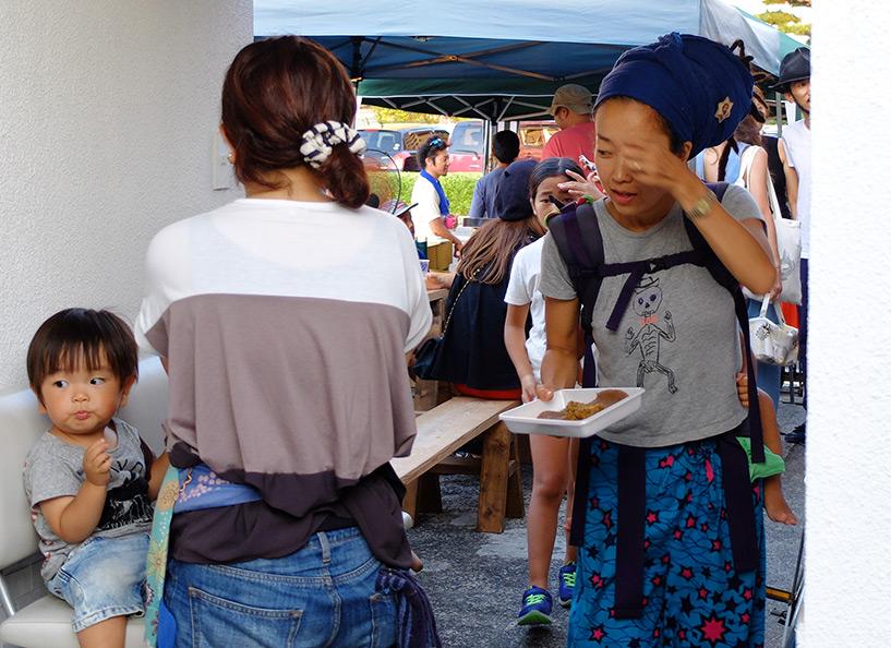 une mère de famille japonaise rasta, avec son bébé sur le dos